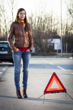 warning triangle: Woman with broken car seeking help Stock Photo