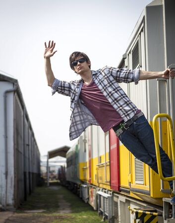 Young man hanging from the train wearing glasses