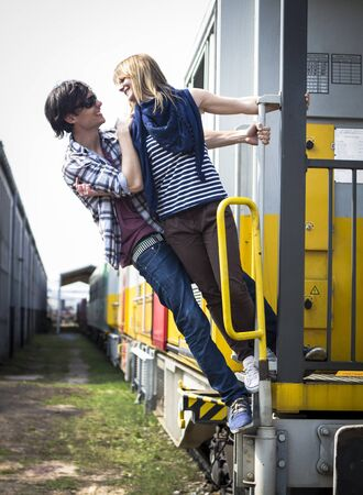 Young couple hanging from the train wearing glasses