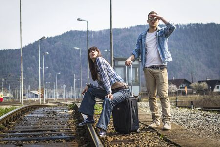 Young couple waiting for the train in lost station photo