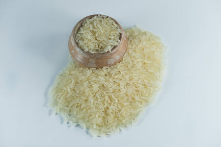 Rice in a wooden bowl on white background photo