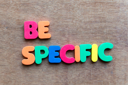 definite: be specific colorful word in the wooden background