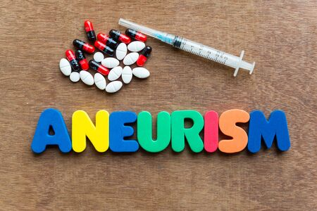 aneurism: aneurism colorful word in the wooden background