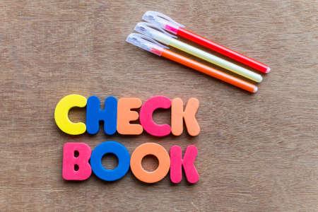 chequera: chequera colorido de la palabra en el fondo de madera