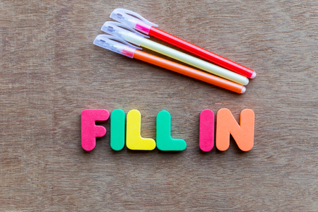 fill fill in: fill in colorful word on the wooden background Stock Photo