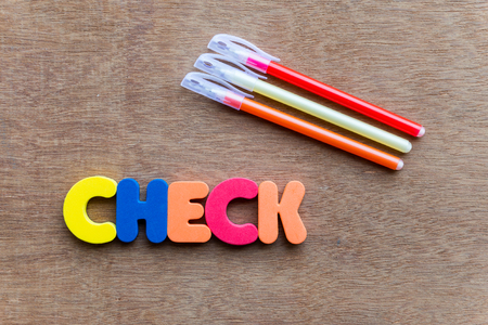 assay: check colorful word on the wooden background