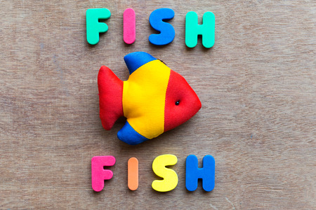 gel capsule: fish fish colorful word on the wooden background