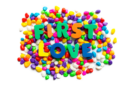 the first love: first love words on the colorful stone and white background Stock Photo