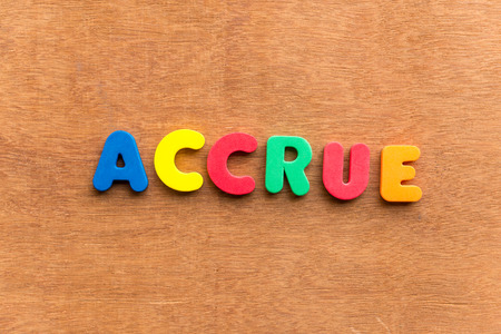 accrue: accrue colorful word on the wooden background