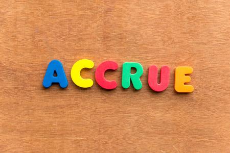 accrue: accrue colorful word on the wooden background