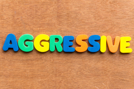 aggressive: aggressive colorful word on the wooden background Stock Photo