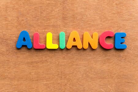 international business agreement: alliance colorful word on the wooden background