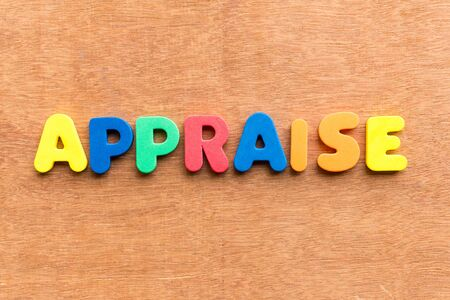 appraise: appraise colorful word on the wooden background Stock Photo