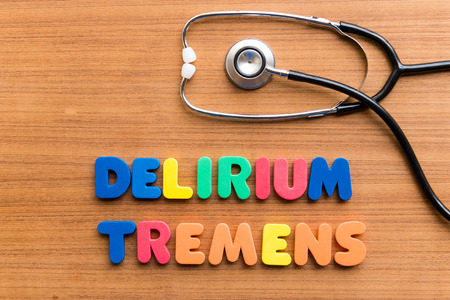 delirium: DELIRIUM TREMENS colorful word on the wooden background Stock Photo