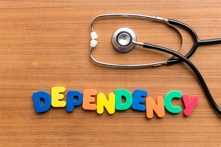 dependency: DEPENDENCY colorful word on the wooden background Stock Photo