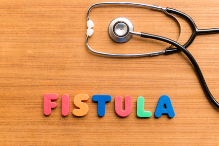 horrified: fistula colorful word on the wooden background
