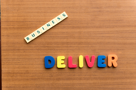 deliver: deliver colorful word on the wooden background Stock Photo