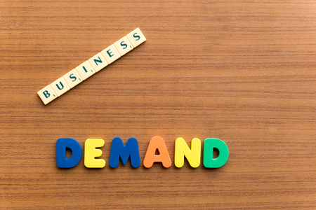 in demand: demand colorful word on the wooden background