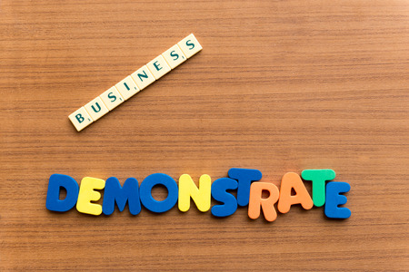 demonstrate: demonstrate colorful word on the wooden background Stock Photo