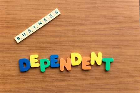 dependent: dependent colorful word on the wooden background