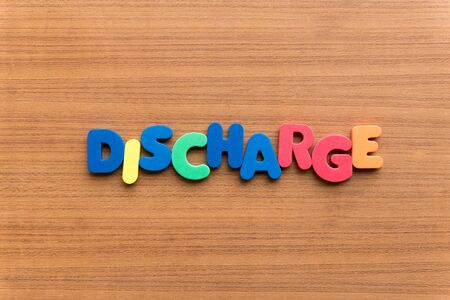 discharge: discharge colorful word on the wooden background Stock Photo