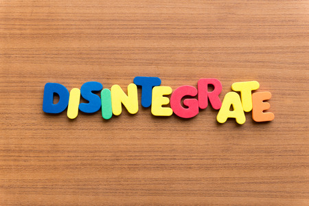 disintegrate: disintegrate colorful word on the wooden background Stock Photo