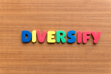 diversify: diversify colorful word on the wooden background