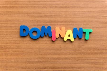 Dominante bunten Wort auf dem hölzernen Hintergrund Standard-Bild - 38857705