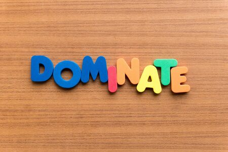 to dominate: dominate colorful word on the wooden background
