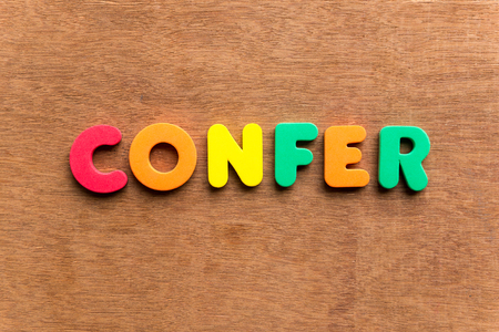 confer: confer colorful word on the wooden background