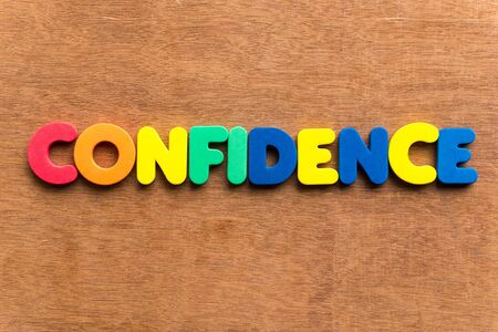 positiveness: confidence colorful word on the wooden background Stock Photo
