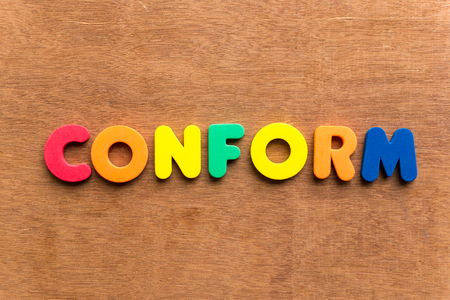 conform: conform colorful word on the wooden background Stock Photo