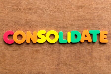 consolidate: consolidate colorful word on the wooden background