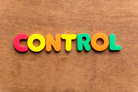 restrain: control colorful word on the wooden background Stock Photo