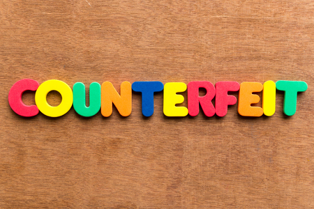 counterfeit: counterfeit colorful word on the wooden background Stock Photo