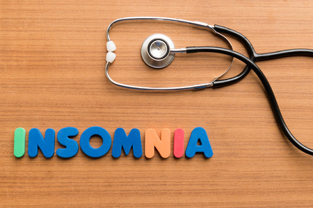 insomnia colorful word on the wooden background