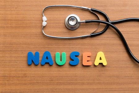 medium group of objects: nausea colorful word on the wooden background Stock Photo