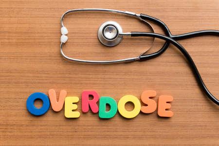 sobredosis: palabra colorido sobredosis en el fondo de madera Foto de archivo