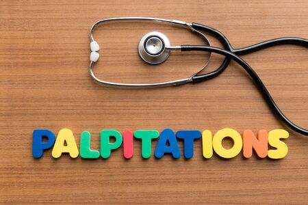 palpitations: palpitations colorful word on the wooden background