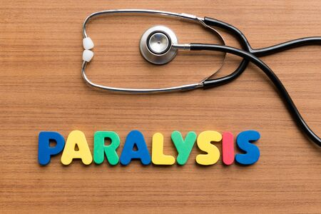 paralysis: paralysis colorful word on the wooden background