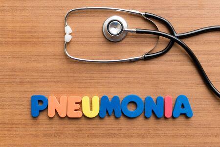 pneumonia: pneumonia colorful word on the wooden background Stock Photo