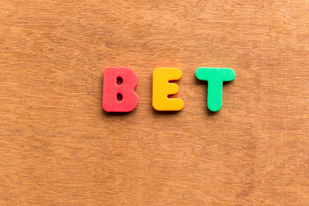 bet: bet colorful word on the wooden background