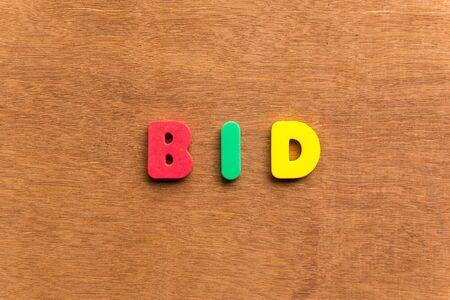 bid: pujar palabra colorida en el fondo de madera