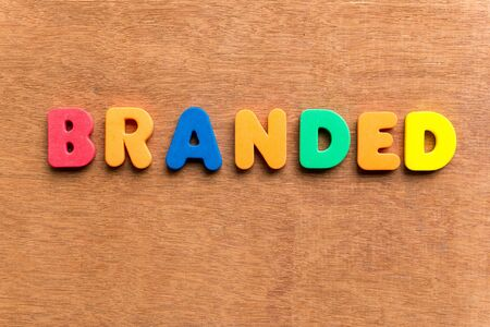 branded: branded colorful word on the wooden background
