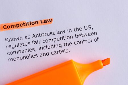 antitrust: competitive law word highlighted on the white paper