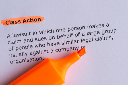 class action word highlighted on the white paper Фото со стока