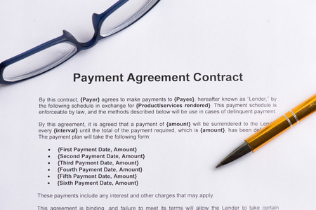 payment agreement contract  on the white paper with pen photo