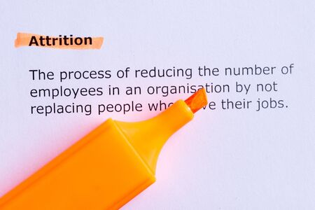 attrition: attrition  word highlighted  on the white paper Stock Photo