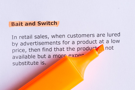 bait and switch   word highlighted  on the white paper Фото со стока