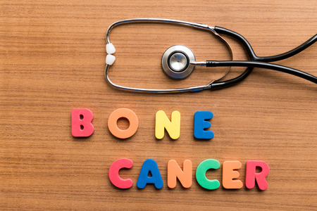 bone cancer: bone cancer  colorful word with stethoscope on wooden background Stock Photo